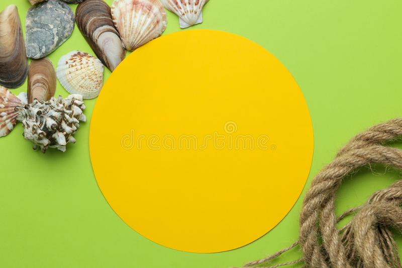 Summer frame. Paper frame for your text, rope and seashells on a bright green background. top view royalty free stock photo