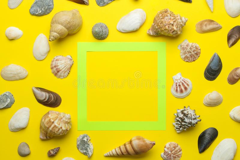 Summer frame. Paper frame for your text and seashells on a bright yellow background. top view stock images