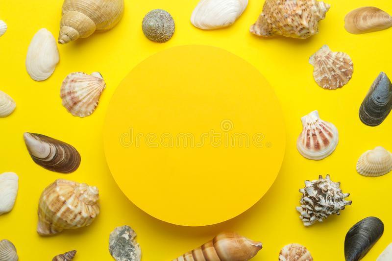 Summer frame. Paper frame for your text and seashells on a bright yellow background. top view stock photo