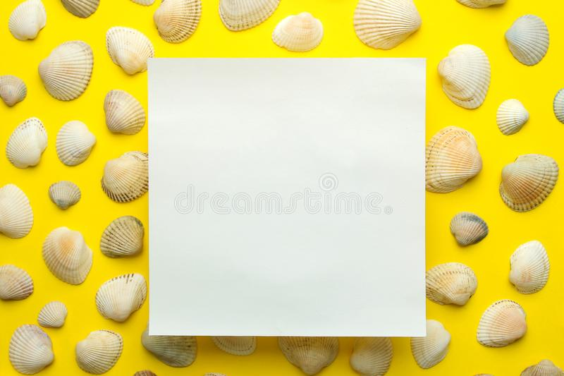 Summer frame. Paper frame for your text and seashells on a bright yellow background. top view royalty free stock image