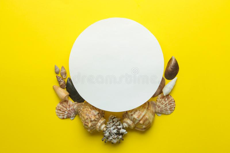 Summer frame. Paper frame for your text and seashells on a bright yellow background. top view stock photography