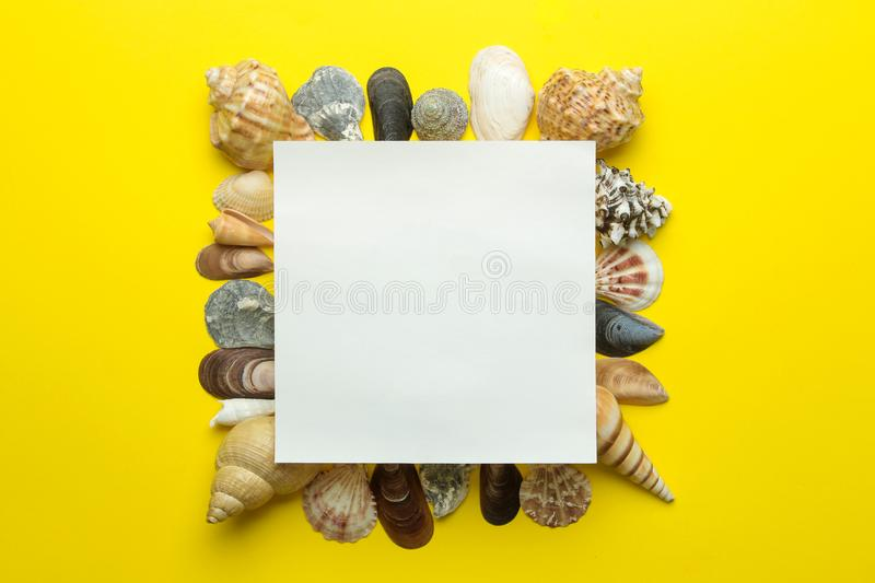 Summer frame. Paper frame for your text and seashells on a bright yellow background. top view royalty free stock photo