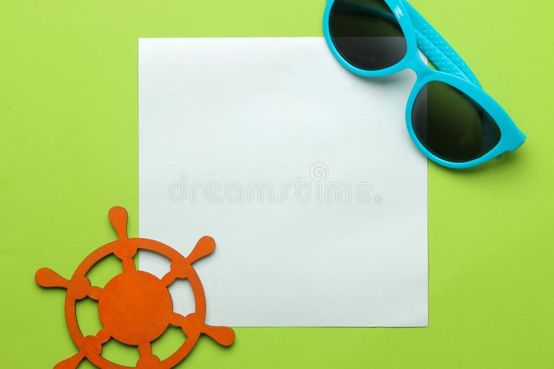 Summer frame. paper frame for your text, sunglasses and decorative nautical steering wheel on a bright green background. top view royalty free stock photos