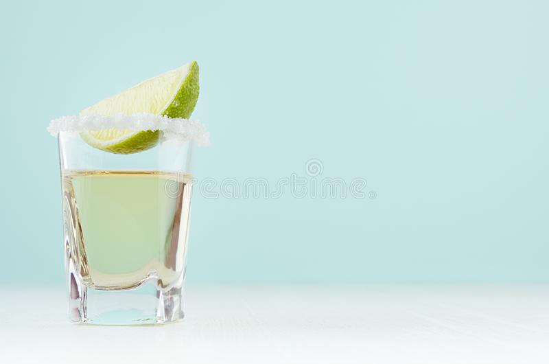 Summer fresh alcohol cocktail with tequila and sour green lime in exquisite shot glass in soft light white and pastel green. royalty free stock images