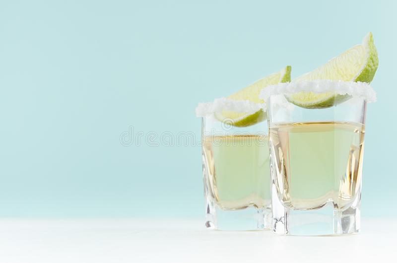 Summer fresh alcohol cocktails with tequila and sour green lime in exquisite shot glass in soft light white and pastel green. Summer fresh alcohol cocktails royalty free stock photo