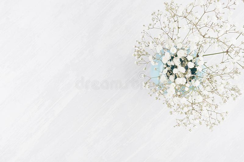 Summer fresh background with airy flowers in blue vase on white wooden board top view with copy space. Summer fresh background with airy flowers in blue vase on royalty free stock images