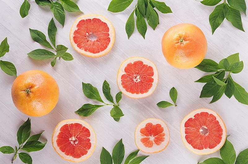 Summer fresh background - round slices pink grapefruits and green leaves on white wood board, top view, pattern. royalty free stock photo