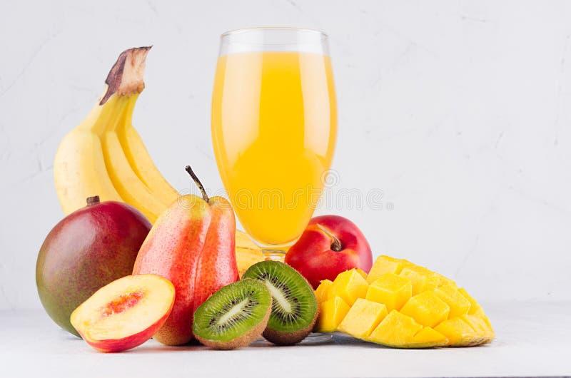 Summer fresh drink of tropical fruits with ripe sliced mango, kiwi and banana on white wood table, closeup. Summer fresh drink of tropical fruits with ripe royalty free stock photos