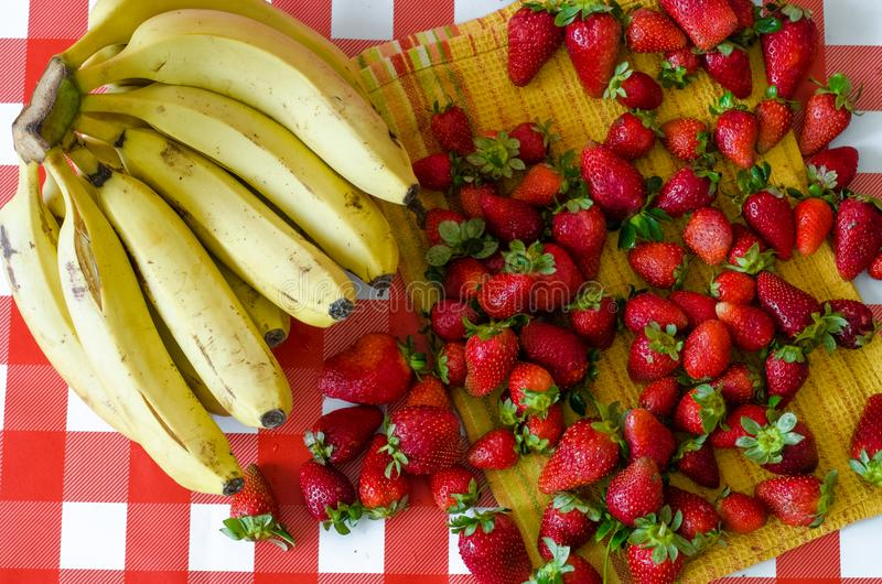 Summer fresh fruits, a lot of ripe strawberries and big bunch of yellow bananas, on yellow kitchen towel. On red checkered background royalty free stock photography