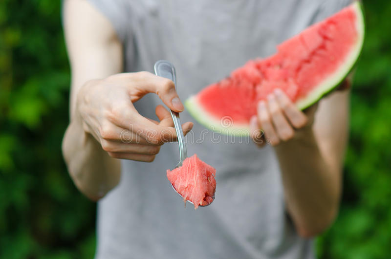 Summer and fresh watermelon theme: a man holds out a spoon with watermelon on the green background royalty free stock photos
