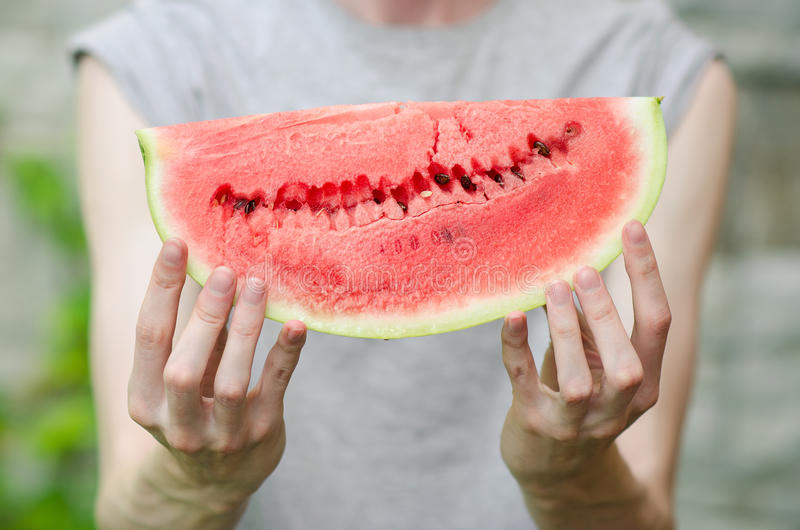 Summer and fresh watermelon theme: a man holds a slice of watermelon on a green background stock images