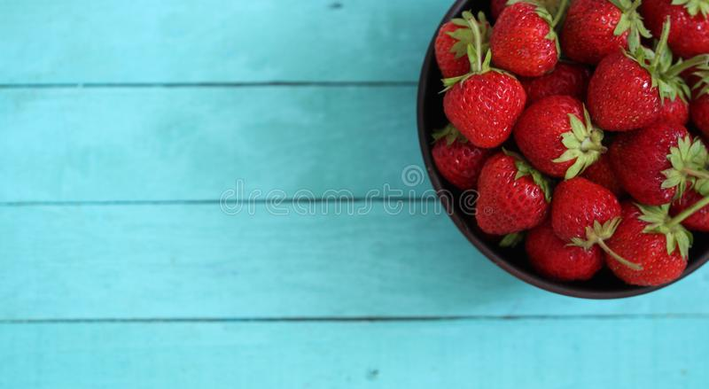 Summer fruit background, fresh strawberries in bowl on wooden table top view stock images