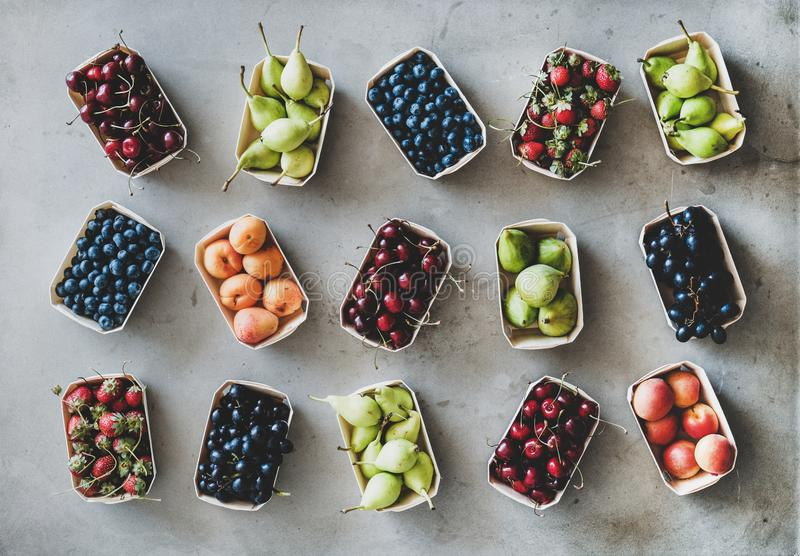 Flat-lay of various fruits and berries over grey concrete background stock photography