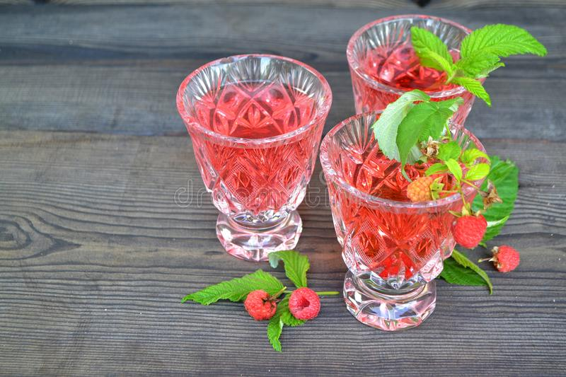Summer fruit jelly in crystal bowl with fresh raspberries, on black wooden table. Diet healthy breakfast stock photo