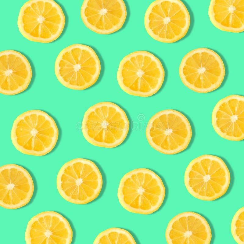 Lemon slice fruit pattern on a teal green background. Summer fruit pattern of lemon slices on a teal background stock photos