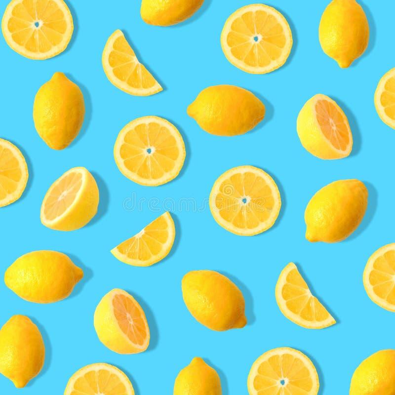 Lemon and lemon slice fruit pattern on a bright blue background. Summer fruit pattern of lemons and lemon slices on a bright blue background royalty free stock photography