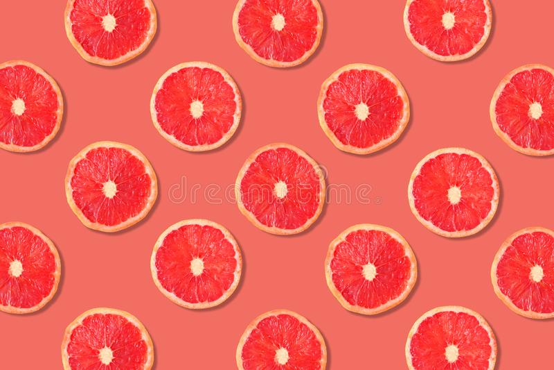 Fruit pattern of pink grapefruit slices on a rose color background stock image