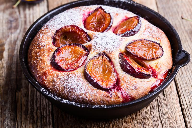 Summer fruit pie. With fresh plums in cast iron skillet on rustic wooden table royalty free stock image