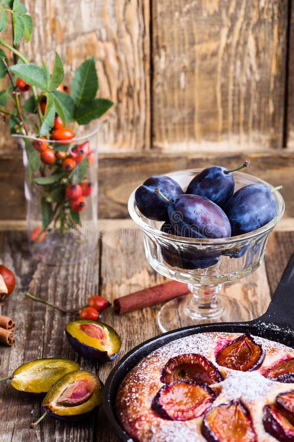 Summer fruit pie. With fresh plums in cast iron skillet on rustic wooden table royalty free stock images