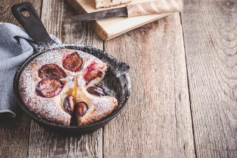 Summer fruit pie. With fresh plums in cast iron skillet on rustic wooden table stock image
