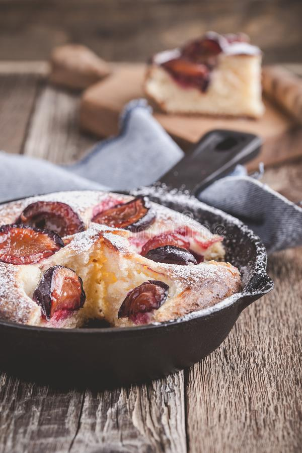 Summer fruit pie. With fresh plums in cast iron skillet on rustic wooden table stock photo