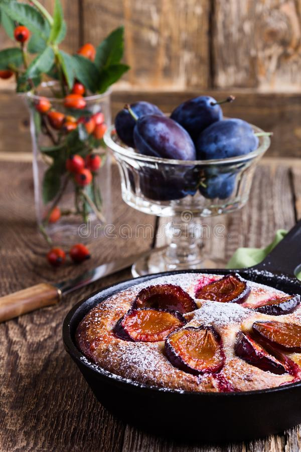 Summer fruit pie. With fresh plums in cast iron skillet on rustic wooden table royalty free stock photography