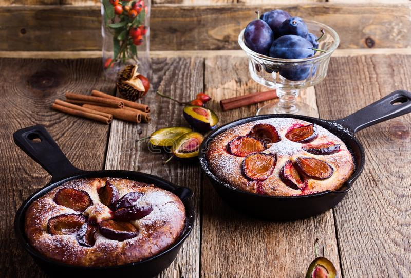 Summer fruit pie. With fresh plums in cast iron skillet on rustic wooden table stock images