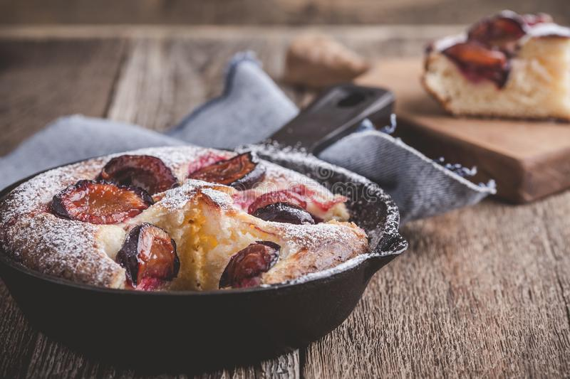 Summer fruit pie. With fresh plums in cast iron skillet on rustic wooden table royalty free stock photos