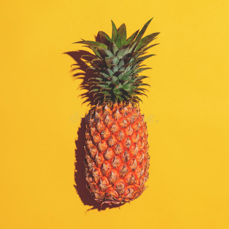 Summer fruit. Pineapple on bright yellow background. stock images