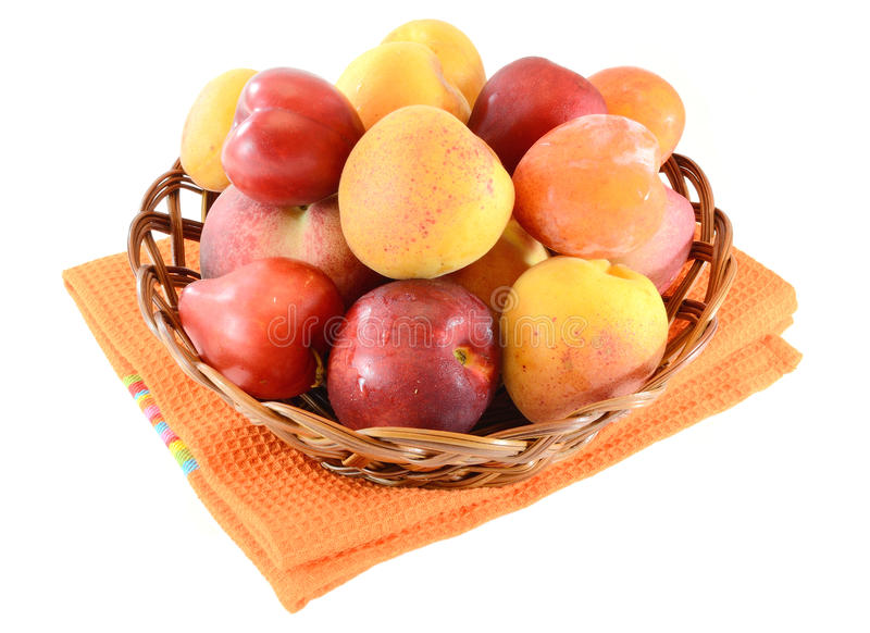 Summer fruits. Wicker basket full of summer fruits:peaches, apricots, plums,prunes.Isolated on white background royalty free stock photos