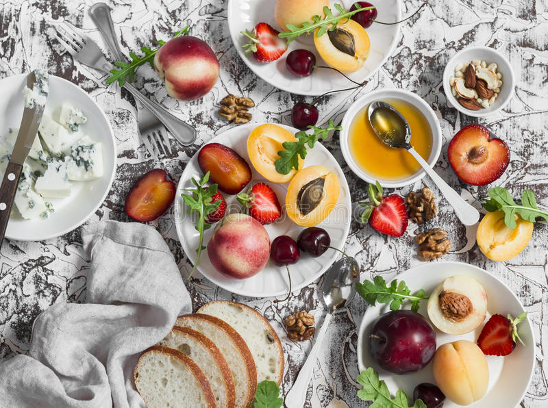 Summer fruits - apricots, peaches, plums, cherries, strawberries and blue cheese, honey, walnuts on a light stone background. Heal stock images