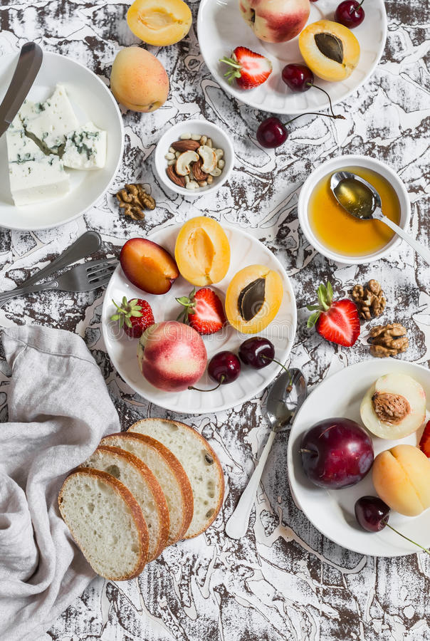 Summer fruits - apricots, peaches, plums, cherries, strawberries and blue cheese, honey, walnuts on a light stone background. Heal. Thy, diet, vegetarian food royalty free stock photo
