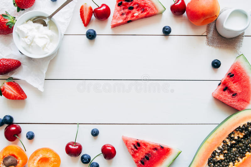 Summer fruits. Fresh juicy berries, watermelon and papaya on the white wooden table, top view. Copy space royalty free stock photos