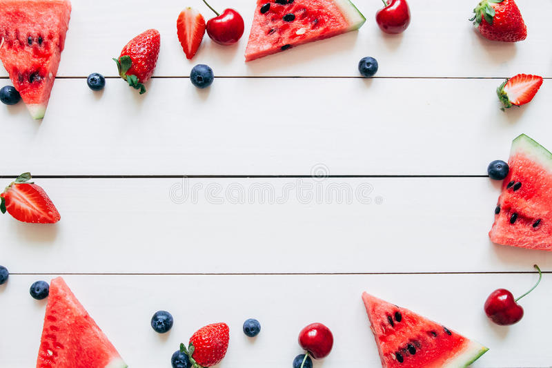 Summer fruits. Fresh juicy berries and watermelon on the white wooden table, top view. Copy space royalty free stock photography