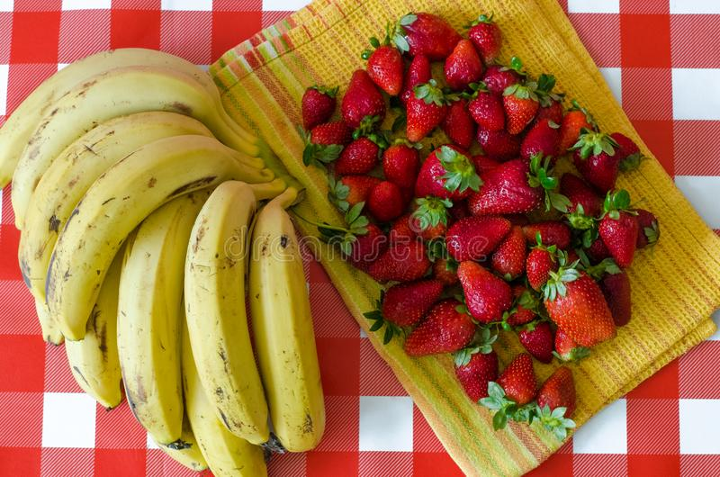 Summer fruits from Israel market, a lot of ripe strawberries and big bunch of yellow bananas. On yellow kitchen towel, on red checkered background stock photo