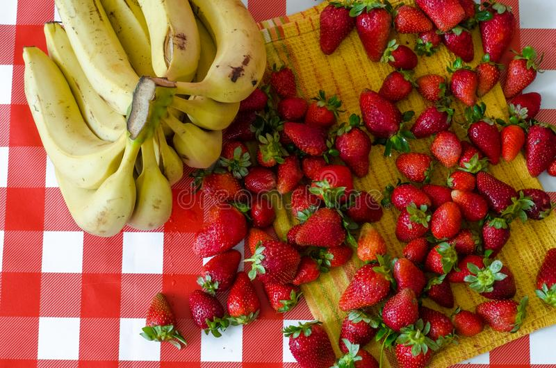 Summer fruits from market, a lot of ripe strawberries. And big bunch of yellow bananas stock image