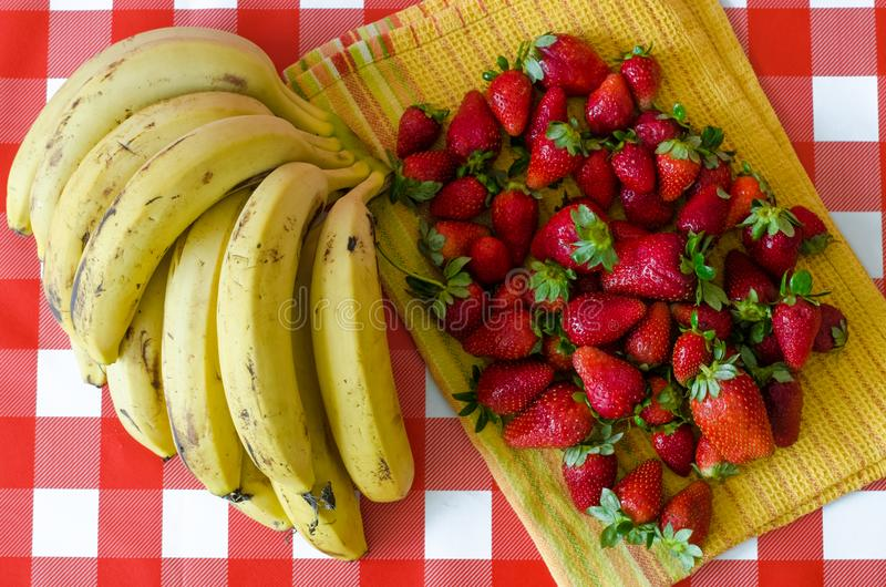 Summer fruits from market, a lot of ripe strawberries and big bunch of yellow bananas. On yellow kitchen towel, on red checkered background stock photos