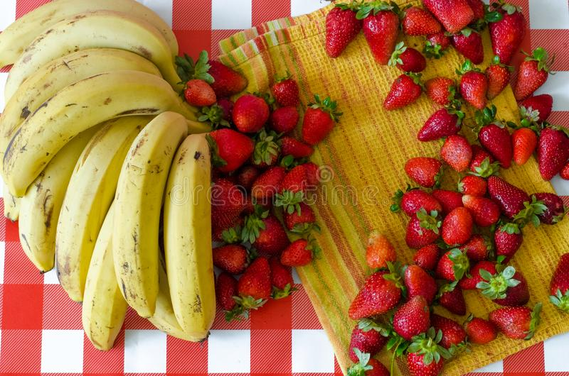 Summer fruits from market, a lot of ripe strawberries and big bunch of yellow bananas. On yellow kitchen towel stock images
