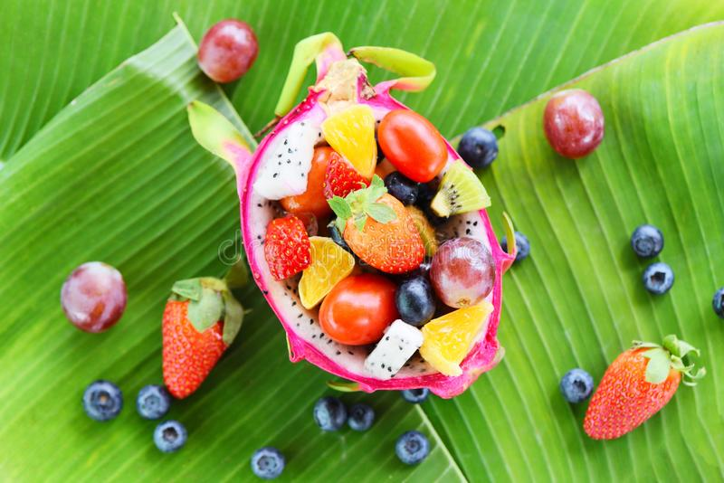 Summer fruits tropical on banana leaf background - Fruit salad bowl served in a dragon fruit and vegetables healthy organic food. Summer fruits tropical on stock photography