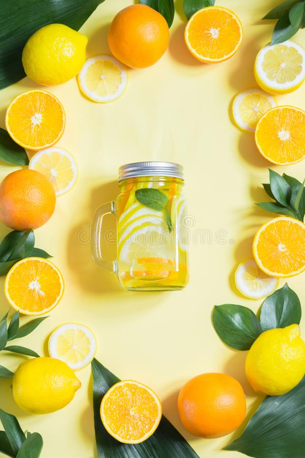 Summer fruits water with lemon, orange, mint and ice in mason jar on yellow. Tropical concept. Top view royalty free stock image