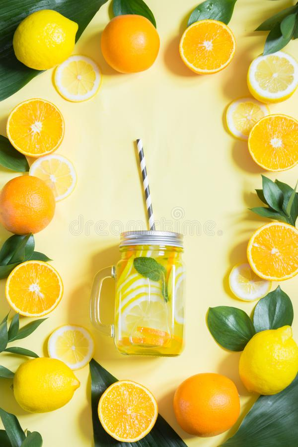 Summer fruits water with lemon, orange, mint and ice in mason jar on yellow. Tropical concept. Top view stock images