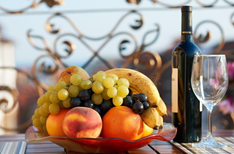 Summer fruits and wine bottle stock image