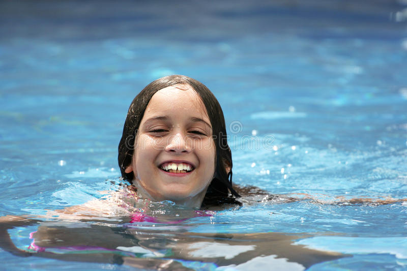 Summer Fun. Young girl in a swimming pool during the summer time stock photos