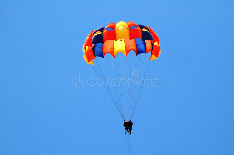 Summer Fun. A couple para-sailing against blue sky royalty free stock images