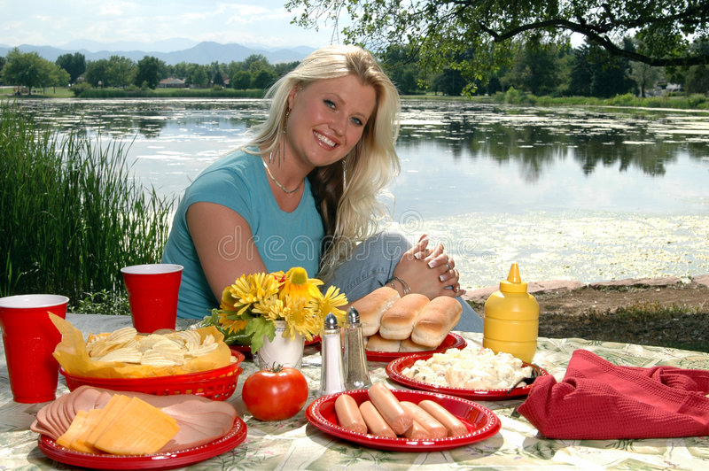 Summer fun. A beautiful blond wmasn sitting at a picnic table by a lake royalty free stock image