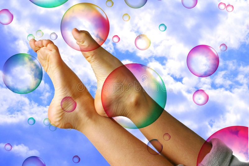 Summer fun. Summer holiday feeling - a child´s bare feet and legs leisurely playing with colorful bubbles over blue sky background. Fit for do-nothing, happy stock images