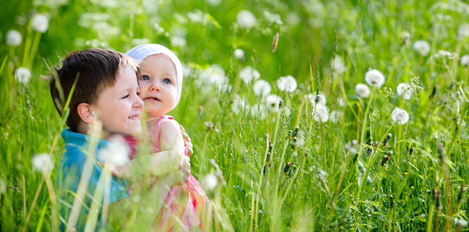 Summer Fun. Brother and little sister playing in green grass at sunny summer day royalty free stock images
