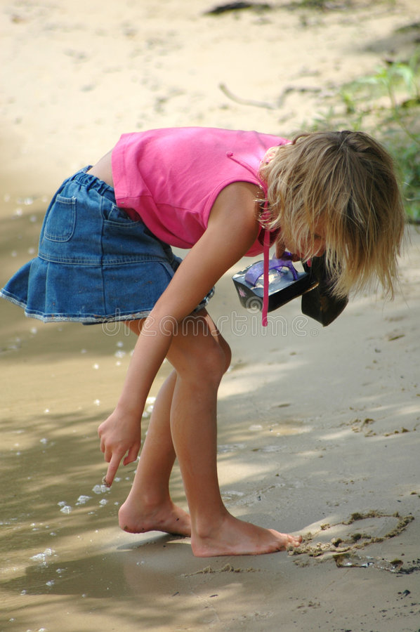 Summer Fun. Young girl make designs and words in the sand stock photos