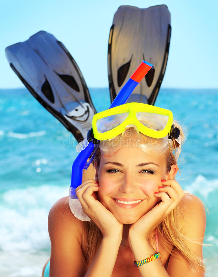 Summer fun on the beach. Beautiful female closeup portrait on the beach wearing snorkeling equipment, water sport, healthy lifestyle concept