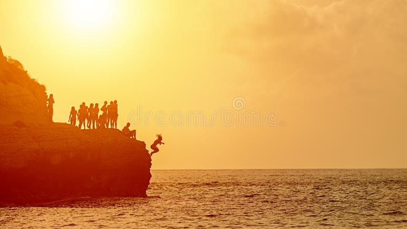 Summer fun with best friends cliff jumping into ocean, young people silhouette enjoying time together swimming at sunset and jump stock images